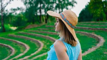 Young woman in straw hat in sunny garden photo