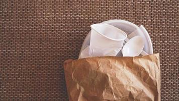 Platos de plástico blanco arrugado en un paquete de papel sobre fondo beige foto