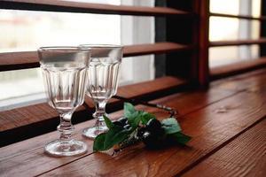 Ventana con un acogedor alféizar de madera, vasos vacíos y decoración floral. foto
