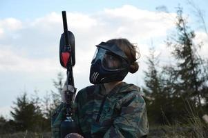 Paintball sport player girl in protective camouflage uniform and mask photo