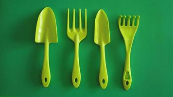 Set of green garden tools on green background photo