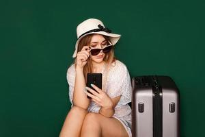 Beautiful girl sits near a suitcase. Waiting for departure photo