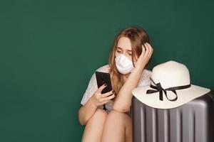 niña turista en una máscara médica se sienta con equipaje foto