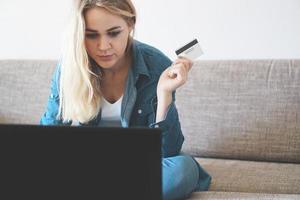 Mujer bonita joven que trabaja con un portátil y una tarjeta de crédito en casa foto