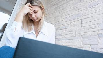 Woman looks at her laptop with a pained worried expression photo