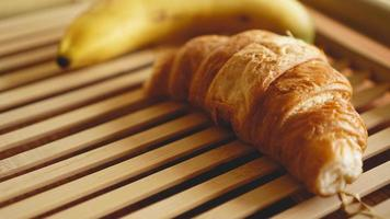 Banana and croissant on rustic wooden background photo