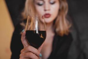 Beautiful woman with glass wine - selective focus photo