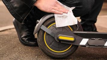un hombre limpia su scooter eléctrico con un paño blanco húmedo. foto