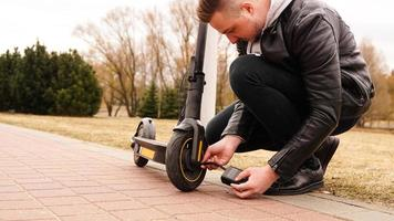 A man pumps air into the wheel of an electric scooter photo