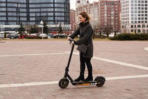 Beautiful girl in a coat rides electric scooter around the city photo