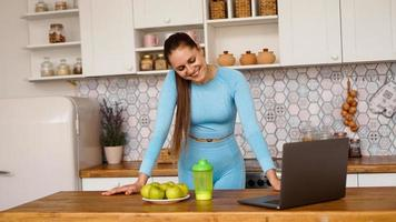 Smiling woman using computer in modern kitchen. photo