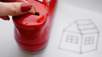 mano dejando caer una moneda en la hucha. dibujando una casa en una hoja foto