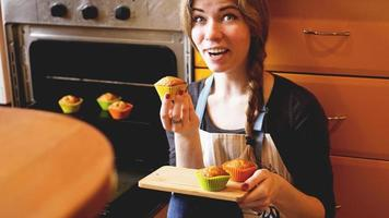 Beautiful blonde woman showing muffins in a kitchen photo