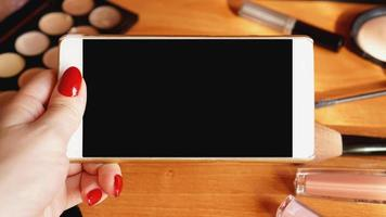 Smartphone with empty screen and cosmetics on wooden background photo