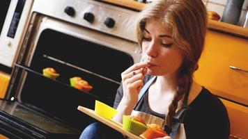 Beautiful blonde woman showing muffins while eating one in a kitchen photo