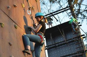 Active young woman on rock wall in sport center photo
