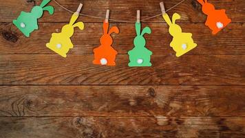 Easter background. Garland of paper rabbits on a wooden background. photo