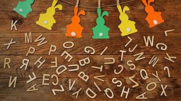 fondo de pascua. Guirnalda de conejos de papel y letras sobre madera. foto