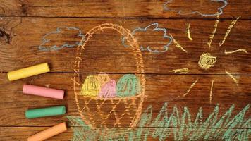 Drawing with crayons on a wooden background. Easter eggs in a basket photo