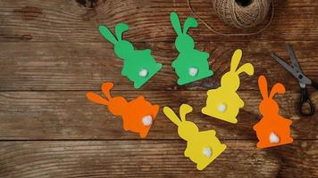 Easter bunnies made of paper on a wooden background. Create a decor photo