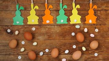 Happy Easter background. Garland of paper rabbits on a wooden photo