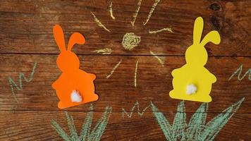 Two Easter bunnies made of paper. Drawn with colored chalk grass photo