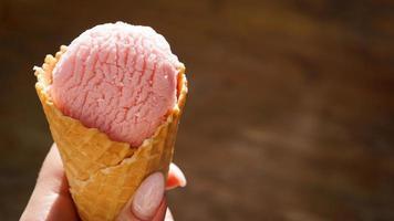 Close up image of woman hand holding raspberry ice cream photo