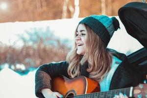 Girl playing guitar sitting on car trunk photo