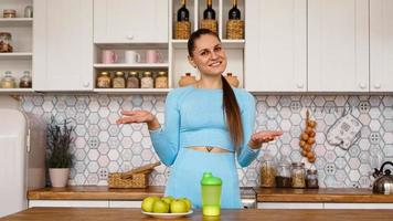 Athletic woman talks about healthy eating in the kitchen and laughs photo