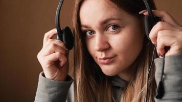 retrato de una joven con una sudadera con capucha y con un auricular. centro de llamadas foto