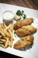 British traditional fish and chips meal on classic wood table photo