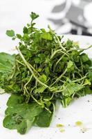 Ensalada de hojas verdes de berros y espinacas orgánicos frescos simples en un plato foto