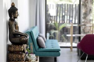 Bronze Buddha statue interior design detail in modern Asian home living room photo