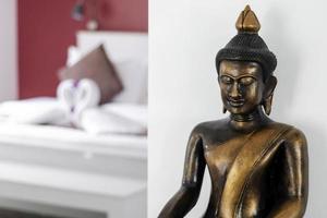Estatua de Buda de bronce, detalle de diseño de interiores en la moderna sala de estar de la casa asiática foto
