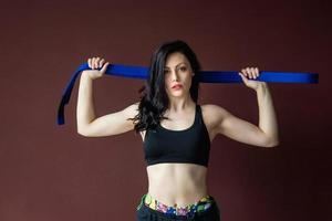 Beautiful athletic woman with blue belt on the wall background photo