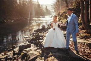 Pareja de novios cogidos de la mano en el fondo de los ríos en las puestas de sol foto