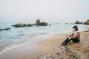Woman tourist in hat sitting on beach looking at sea photo