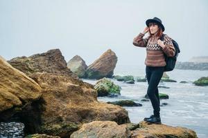 Mujer turista con sombrero con mochila sobre rocas sobre un fondo de mar foto