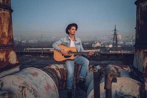 El hombre tocando la guitarra con sombrero en el fondo antiguo edificio abandonado foto