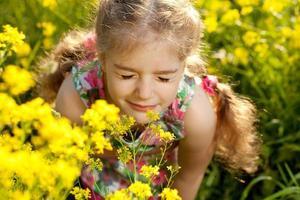 niña rubia inhala aroma de flores foto