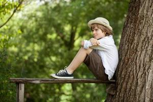 Boy sits on a bench photo