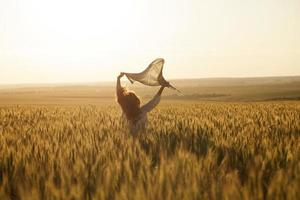 Woman with headscarf in the middle of ripe wheat field photo