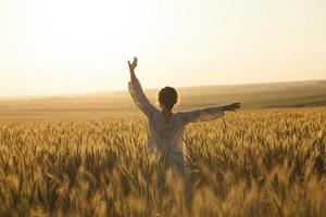 Girl in a dress in the middle of a field of ripe rye photo