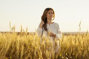 Young woman stands in the middle of a wheat field photo