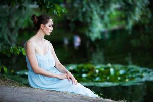 mujer joven triste se sienta en la orilla del estanque foto