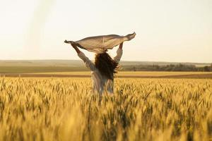 Happy woman with headscarf in the middle of ripe wheat field photo