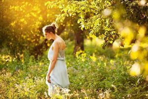 mujer con un vestido azul camina en un huerto de manzanas foto