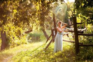 Woman stands near a hedge on a summer evening photo