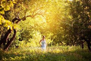 niña con un vestido azul camina por el huerto de la tarde foto