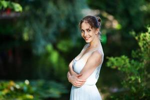 Charming woman in blue dress in the park photo